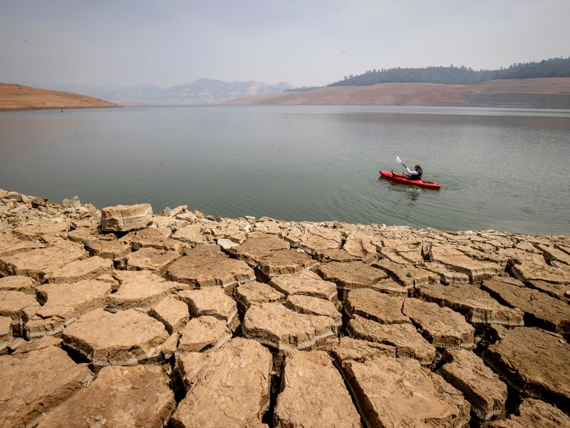 A kayaker fishes in Lake Oroville as water levels remained low due to continuing drought conditions in California on Aug. 22, 2021. AP Photo/Ethan Swope