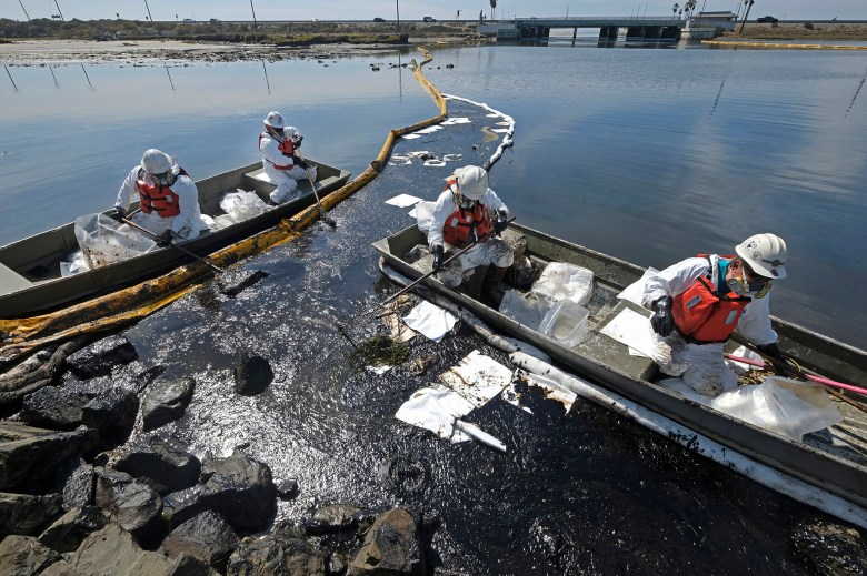 Cleanup contractors deploy skimmers and floating barriers known as booms to try to stop further oil crude incursion into the Wetlands Talbert Marsh in Huntington Beach on Oct. 3, 2021. Photo by Ringo H.W. Chiu, AP Photo