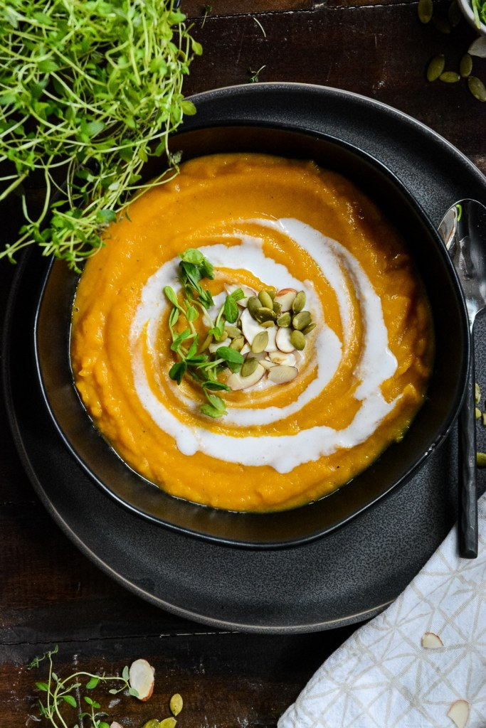 Butternut squash soup in black bowl with creamy swirl, pumpkin seeds and almond slivers.