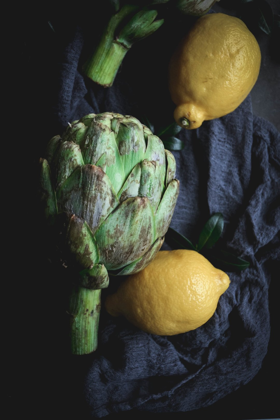 artichoke on dark napkin with whole lemons