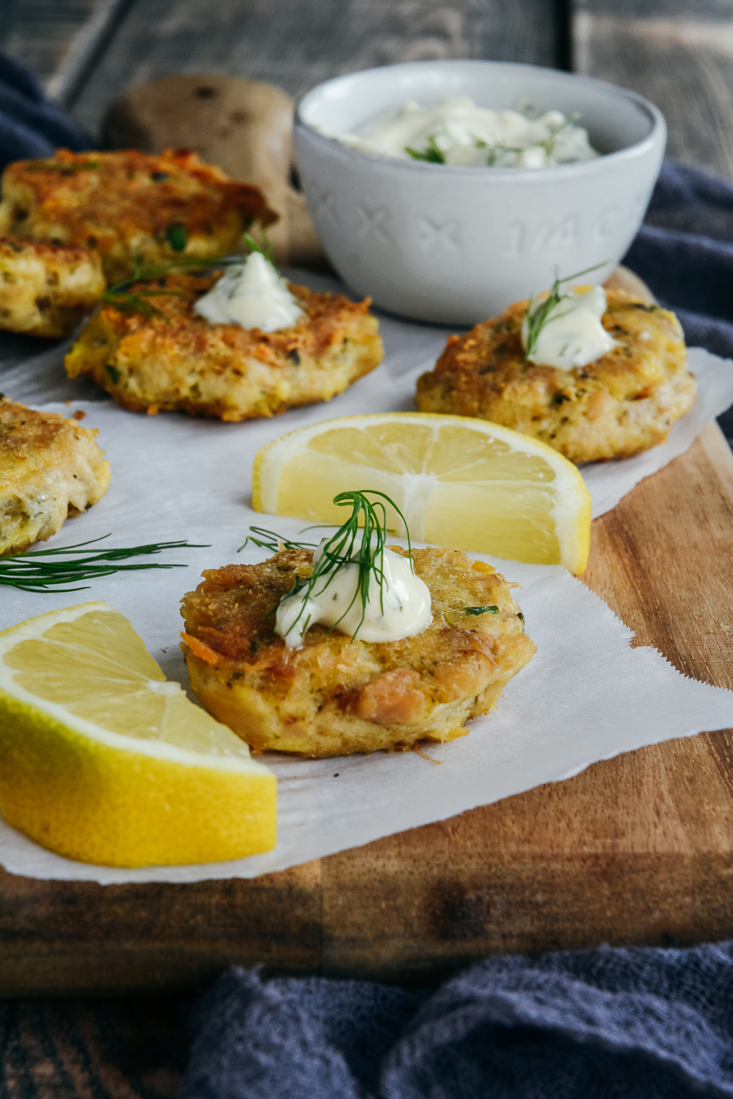 tuna chickpea appetizer bites on cutting board with lemon sauce, dill and bowl or mayo