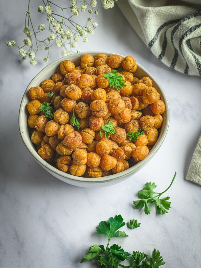 Crispy Roasted Chickpeas in bowl with napkin, and sprinkles with parsley