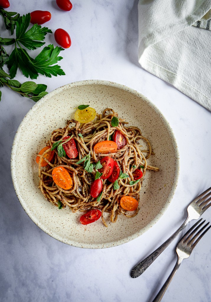 Moroccan Tapenade Spaghetti with Tomatoes and Herbs in bowl with herbs and tomatoes and forks