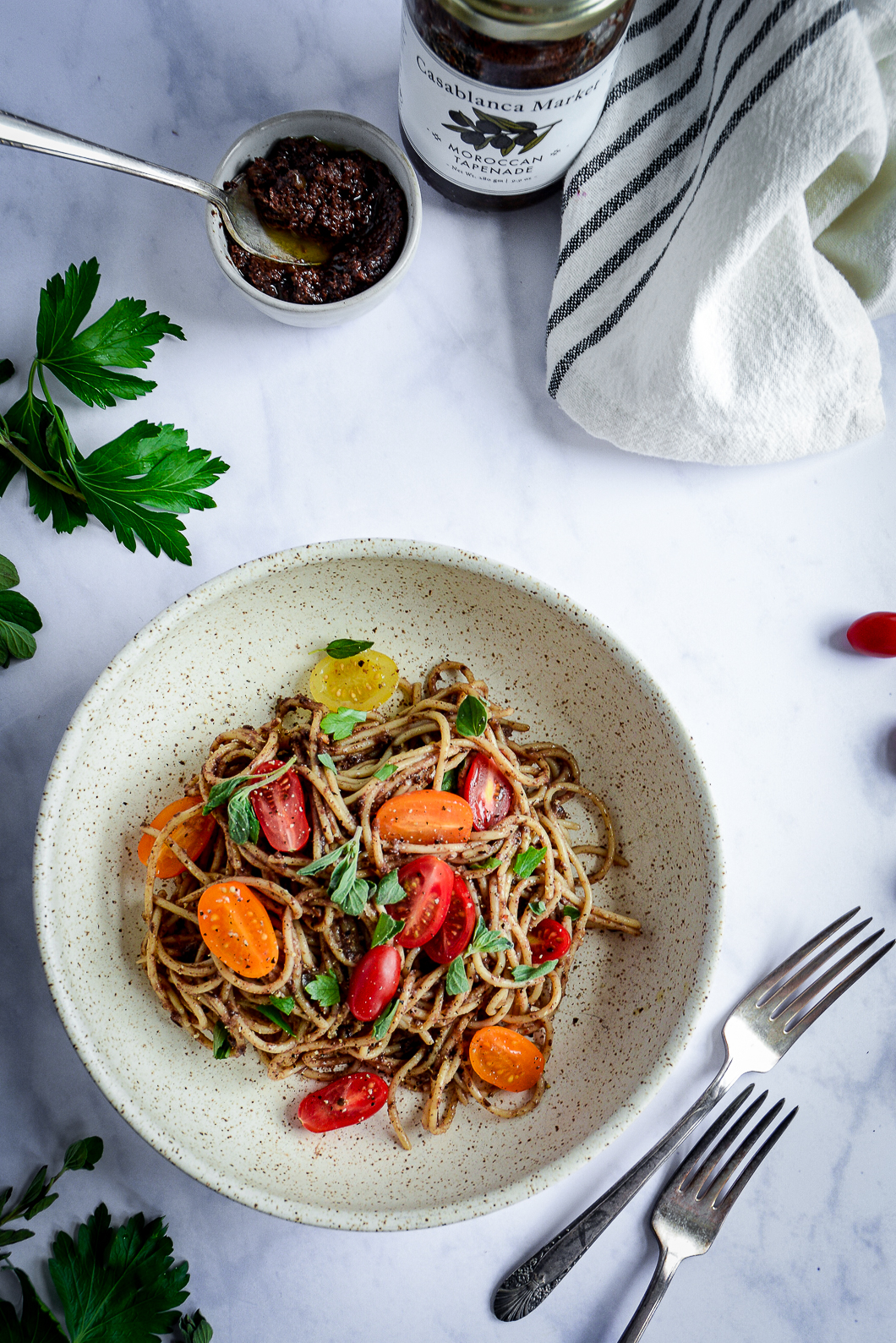 Moroccan Tapenade Spaghetti with Tomatoes and Herbs in bowl with napkin, bowl of tapenade and forks
