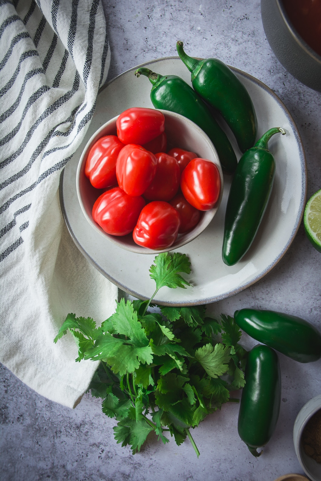 Jalapenos and tomatoes on plate with cilantro lime