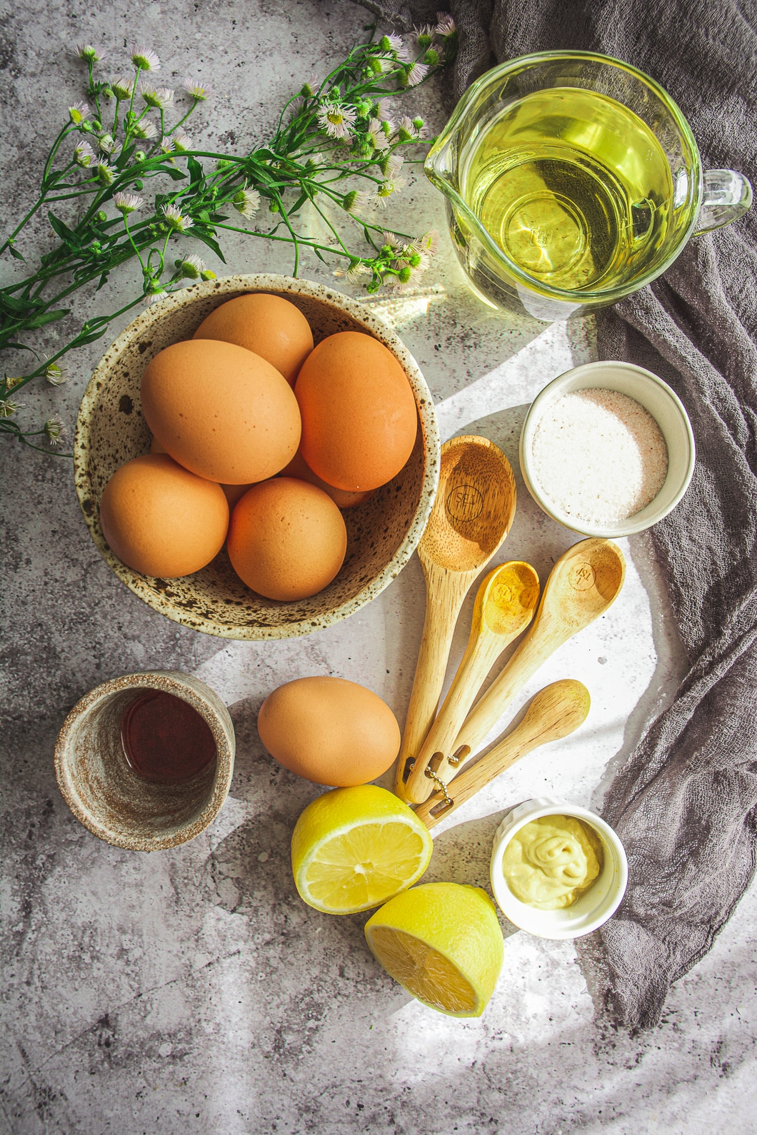Eggs in bowl, olive oil in clear glass container, salt in bowl, wooden spoons, lemons, green and white flowers, napkin