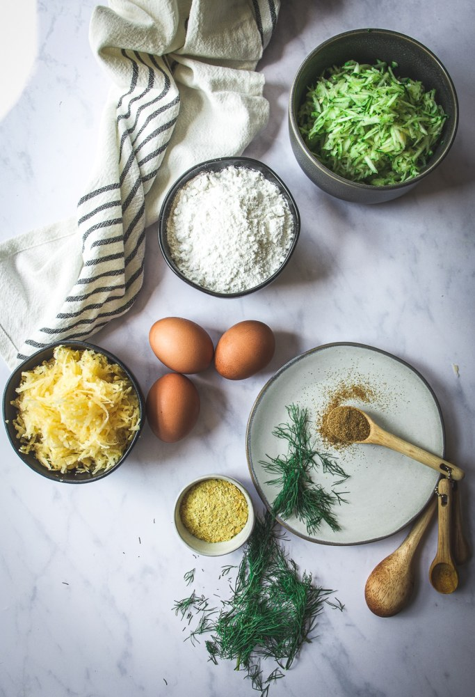 Eggs, grated rutabaga and zucchini, cassava flour, cumin on spoon and nutritional yeast on table