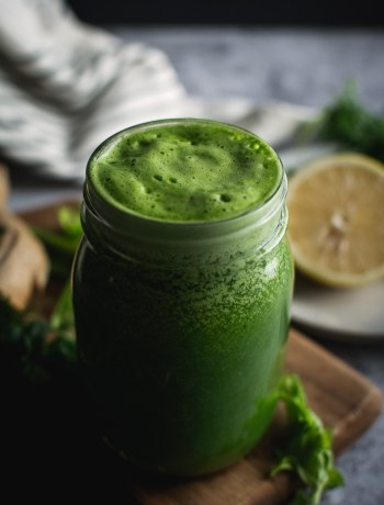 Super Green Parsley and Cilantro Smoothie with straw in glass mug