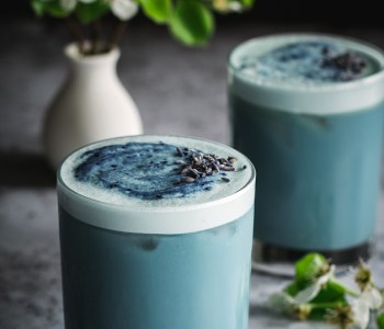 2 blue drinks on table, pear blossoms next to them