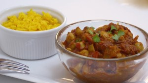 Image shows a dish of chana masala with a side of saffron rice, as described in this recipe on CALMERme.com