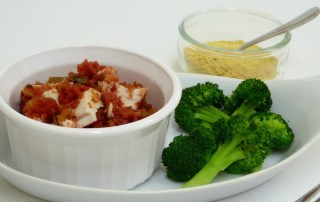 Image shows a dish of white fish cooked in salsa, with a side of broccoli and a small dish of nutritional yeast, as described in this recipe for Fiesta Fish on CALMERme.com