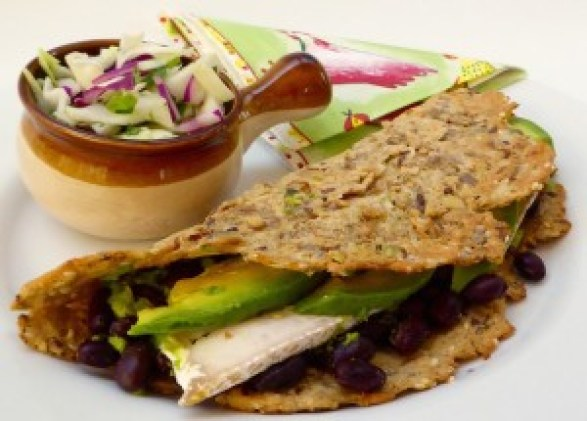 Image shows a gluten-, dairy-, soy-, and refined carb-free wrap, stuffed with black beans, tempeh, avocado, and nut cheese, as described in this recipe on CALMERme.com