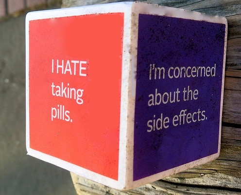 Image shows two sides of a cube with message regarding drug side effects, as described in this post on CALMERme.com