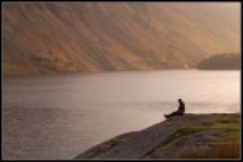 Image shows a person sitting beside a lake, thinking deeply about what lifestyle changes to commit to, as described in this post on CALMERme.com
