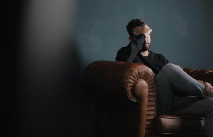 Hombre sentado en un sofá con cansancio mental
