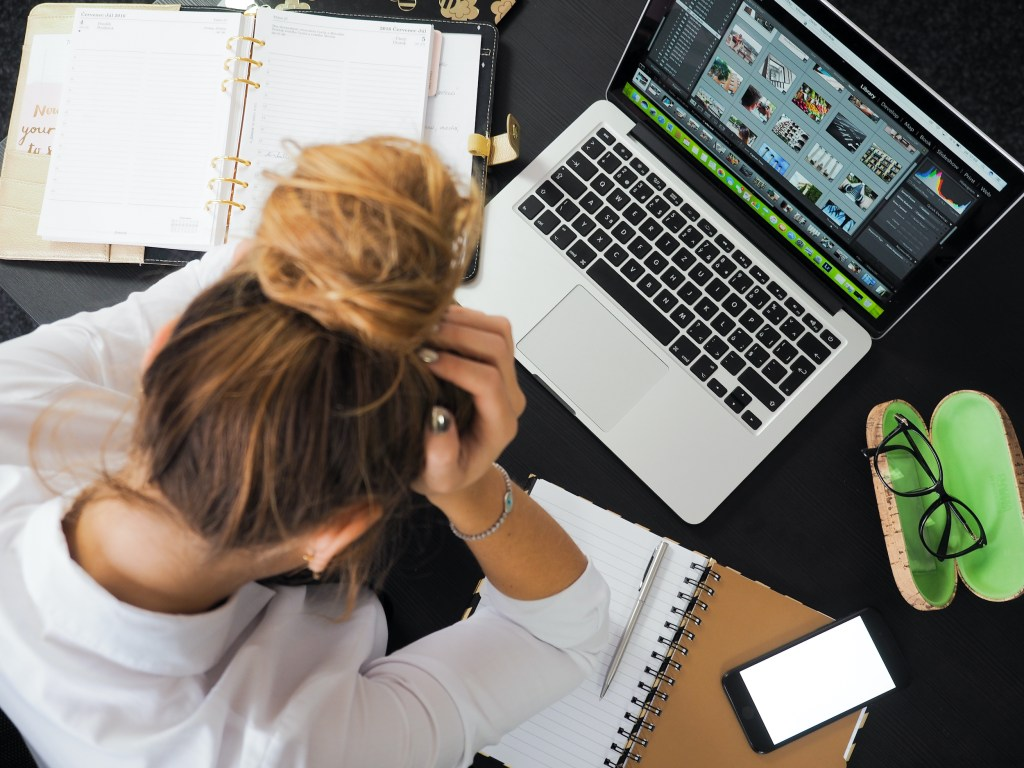 Woman at her computer stressed and pulling her hair out. People with trichotillomania often pull their hair when they feel stress, anxiety, fear, and even boredom.