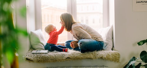 Woman sitting playing with a child.