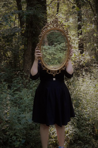 Woman in a forest holding a mirror, obscuring her face. People with Existential OCD can question whether their life is real, whether they are subject to fate, or whether they are feeling genuine feelings.