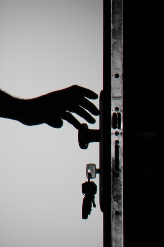 """Hand reaching to lock a door. Checking door locks, locking and unlocking in certain patterns or numbers, or locking while thinking """"safe"""" thoughts are common compulsions for checkers. Get OCD treatment in California or online OCD counseling in Montana here."""
