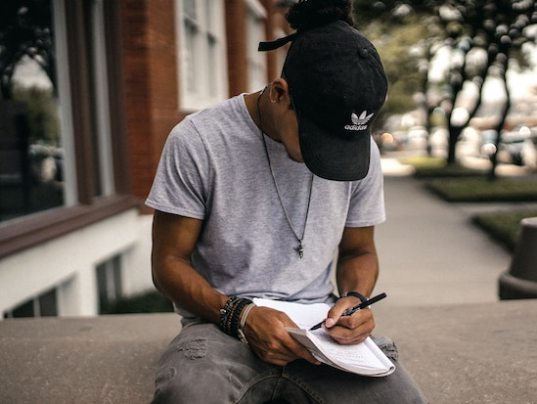 Man writing in a journal. Keeping track of your thoughts can help you find patterns in your Thought Action Fusions. Call the California OCD and Anxiety Treatment Center for treatment in Orange County and online therapy in California and Montana.