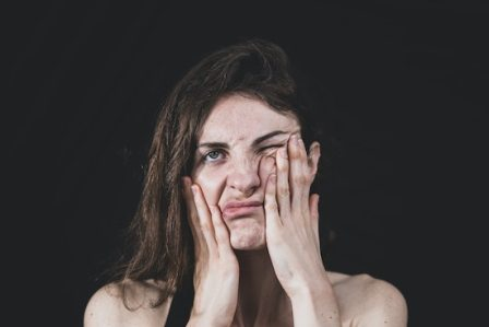 Woman rubbing her face and looking annoyed. Thought Action Fusion can cause people to become overwhelmed by their anxiety and give into irrational behaviors. Call the California OCD and Anxiety Treatment Center for treatment in Orange County and online therapy in California and Montana.