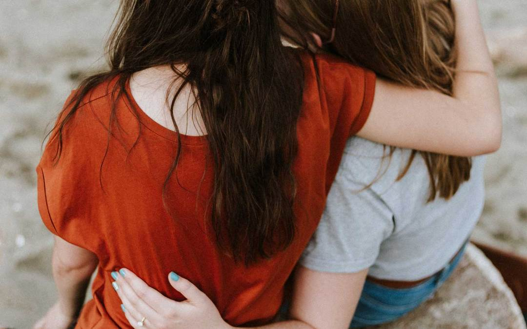 two girls hugging physical affection