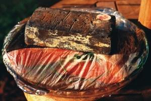 lead ingot on top of plastic wrap covering salmon