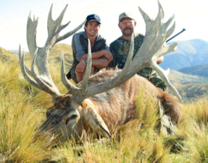 Two hunters and a dead New Zealand Red Stag pose for a picture