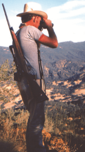 The author stands with a gun over his shoulder and binoculars to his eyes.