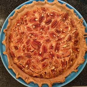 The whole pecan pie in a blue pie dish