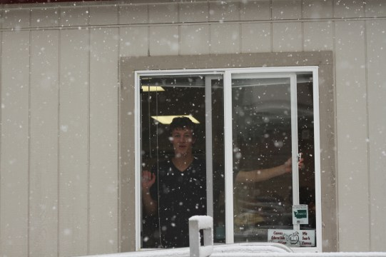 A student looks out the window as snow falls outside.