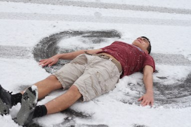 A student makes a snow angel in the freshly fallen snow.