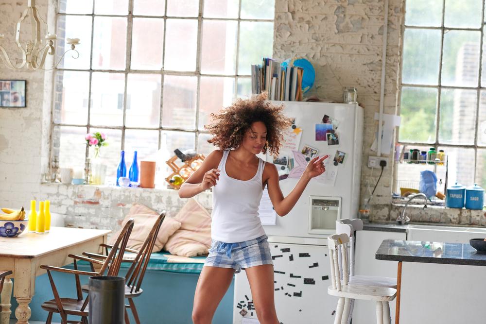 mujer bailando e escuchando canciones para aprender ingles britanico