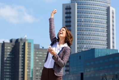 Business woman punching the air with joy