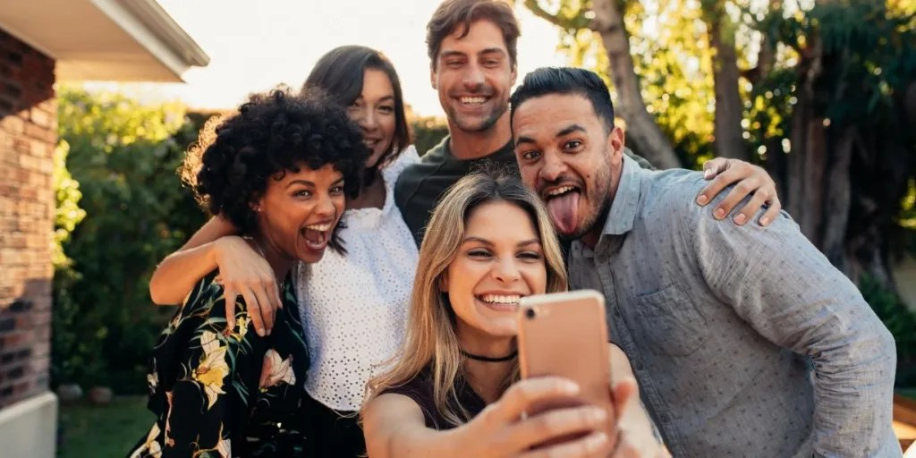 Group of five smiling people taking a selfie outside a residence