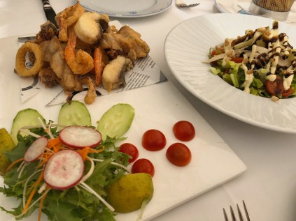 Fried fish, seafood and chicken cesar salad lunch
