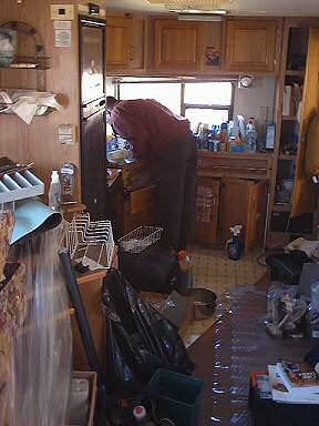 Brent struggles with the kitchen faucet in the messy trailer