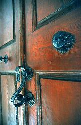 Door handle on red wood door, Paris, photograph by Brent VanFossen