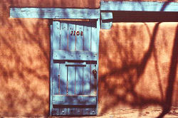 Shadows of nearby trees play across adobe walls and blue door, Santa Fe, New Mexico, photograph by Brent VanFossen