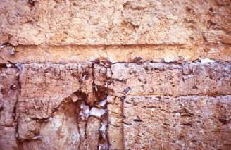 Notes stuffed into the cracks of the Wailing Wall in Jerusalem, photo by Lorelle VanFossen