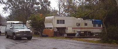 An old fifth wheel trailer stands filthy and falling apart next to where we parked ours