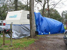 Our trailer covered with blue plastic while we repair leaks in the slideout, photograph by Lorelle VanFossen