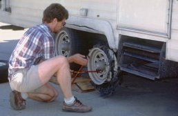Brent repairs the flat tire on the trailer by the side of the highway, photograph by Lorelle VanFossen