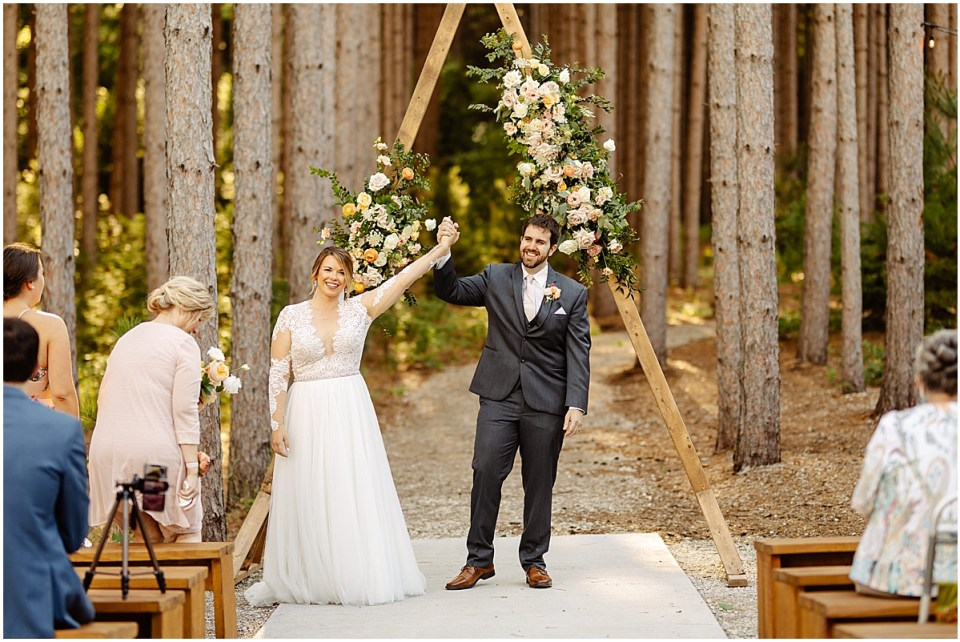Bride and groom outdoor ceremony in pines ay Pinewood Weddings & Events