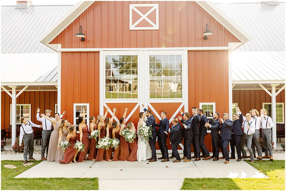 full bridal party joyful pose at red barn farm