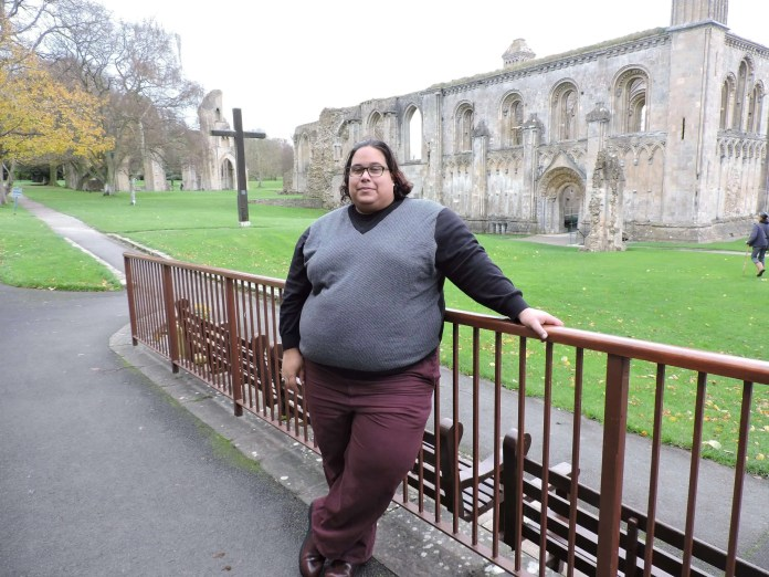 Cameron Cowan standing in front of Glastonbury abbey