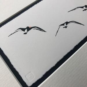 handmade linocut print of black and white oyster catcher birds in flight against unprinted plain white background