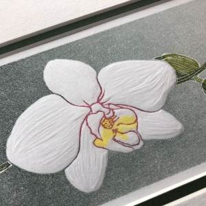 handmade linocut print of a single white orchid bloom with buds against a graded grey background.