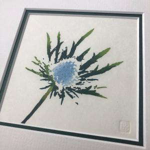 handmade woodblock print of a single blue purple eryngium, or sea holly, flowerhead against a plain pale background