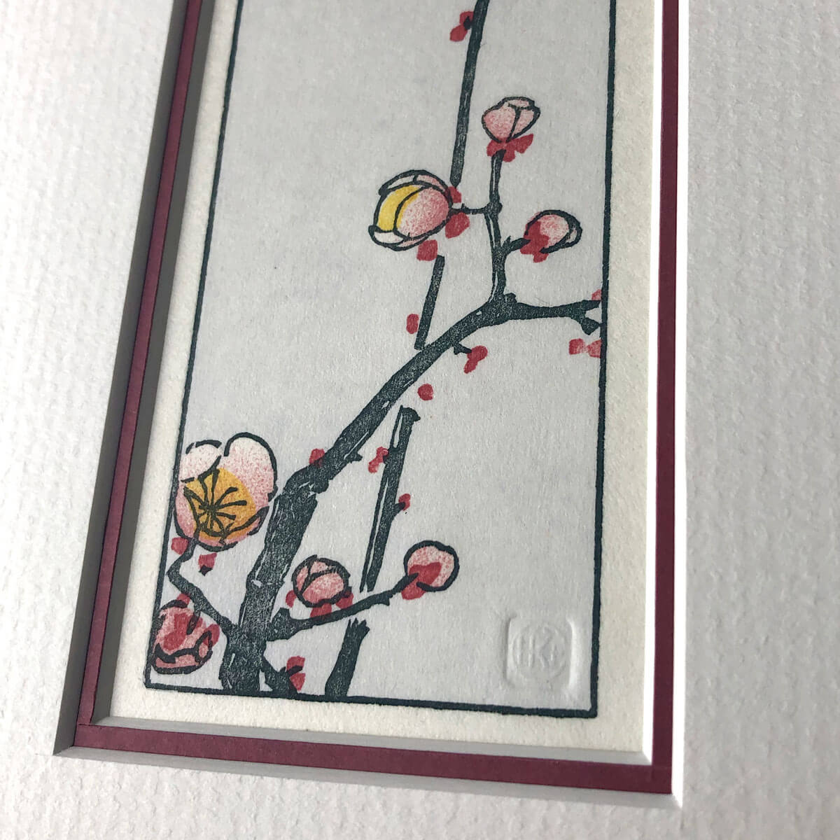 handmade woodblock print of slim branch with pale pink plum blossoms against a pale blue grey background